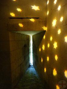 Foto bij affirmeren en visualiseren: sterren geprojecteerd op een muur bij een spleet waar je naar buiten kunt kijken