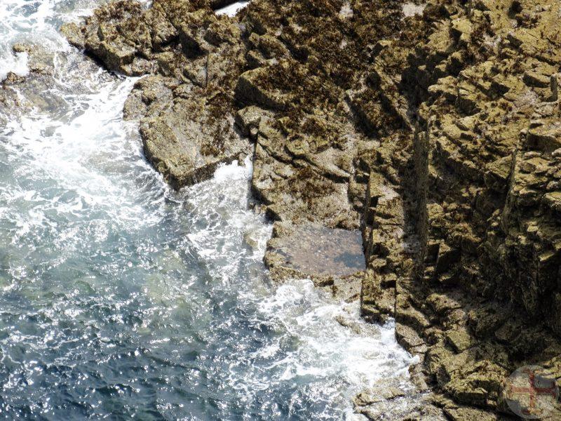"""Afbeelding bij """"Omgaan met angst en de vecht-of-vluchtreactie"""": zicht vanaf hoge rotsen naar beneden met zicht op water"""