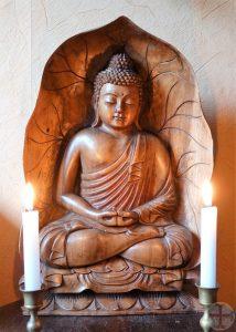 Foto bij mediteren: Boeddha van houtsnijwerk in een koepel