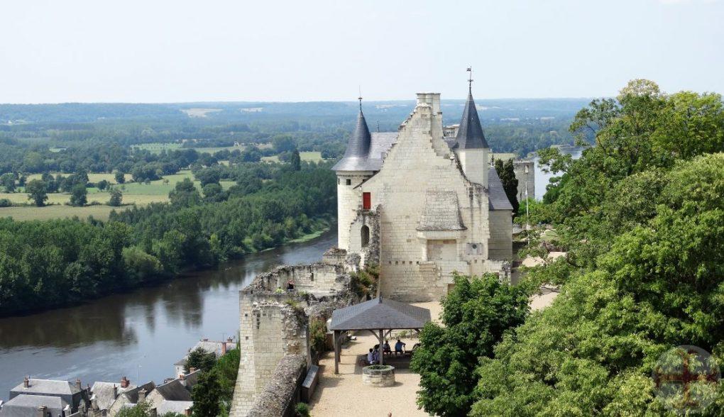 """Afbeelding bij """"Het hier-en-nu"""": kasteel met twee torens aan rivier"""