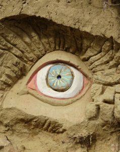 """Afbeelding bij """"Het hier-en-nu"""", een blauw oog gemaakt van o.a. klei tegen een muur, le jardin extraordinaire, Lieurac, FR"""