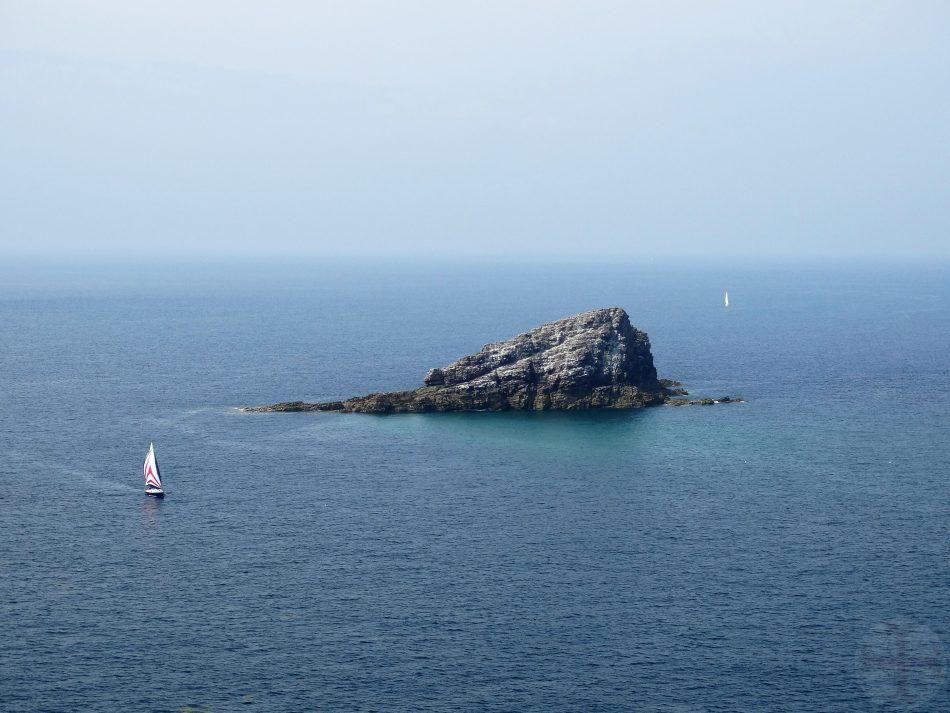 Een sfeerbeeld bij positief denken: op de foto is een rots te zien in zee, onaantastbaar.