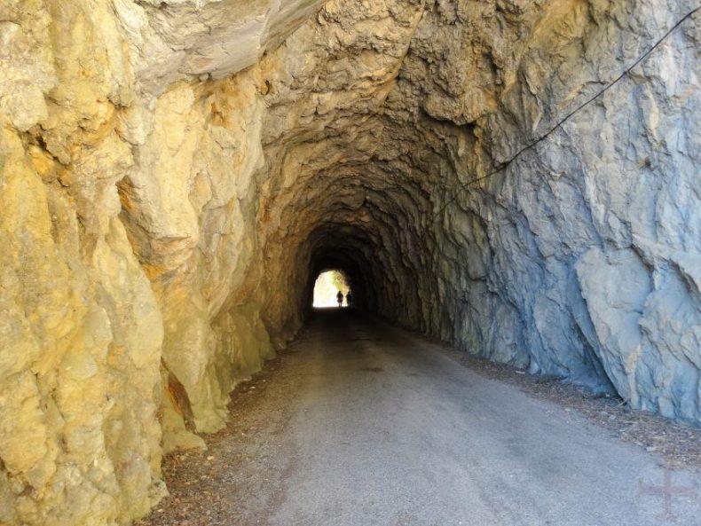 Tunnel met licht aan het eind waarin een persoon staat