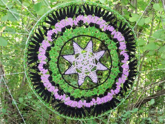 """Afbeelding bij """"Structuur in je leven"""": een mandela van haakwerk in zwart, groen en violet (jardin extraordinaire, Lieurac, FR"""