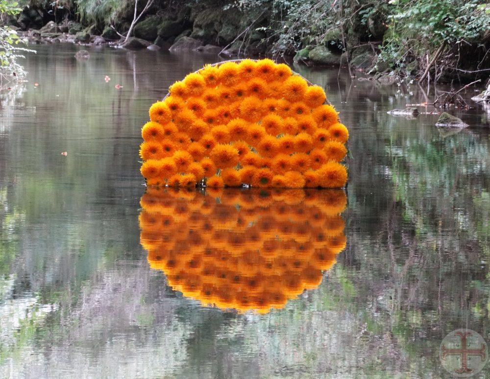 """Foto bij """"Structuur in je leven"""": halve cirkel van gele chrysanten boven water die wordt weerspiegeld in het water (le jardin extraordinaire, Lieurac, FR)"""