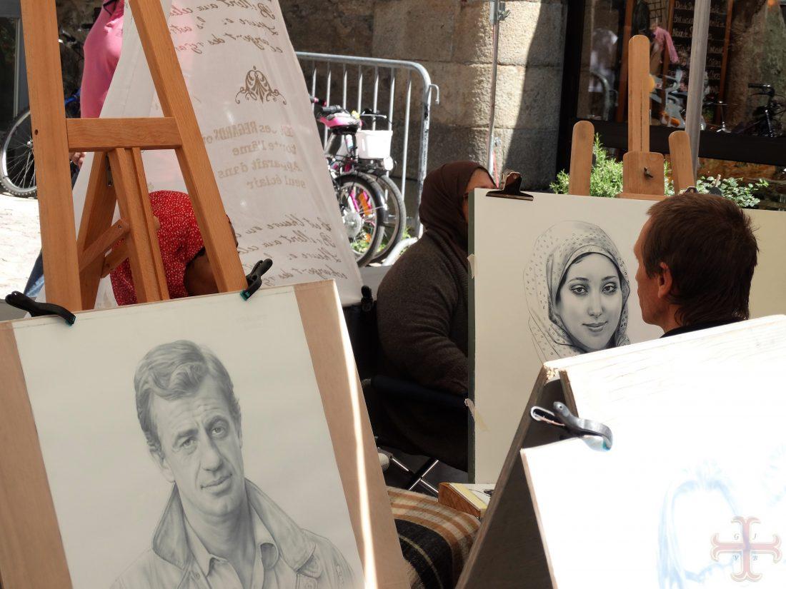 """Afbeelding bij """"Dromen tot doelen maken"""": een tekenaar op de markt tekent een vrouwengezicht na. De vrouw is niet zichtbaar, wel de tekening die wordt gemaakt"""