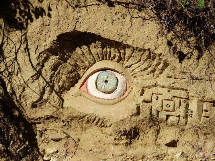 """Afbeelding bij """"Je houden aan de afspraken met jezelf"""": een kunstwerk van klei met een oog in het midden (le jardin estraordinaire, Lieurac, FR)"""