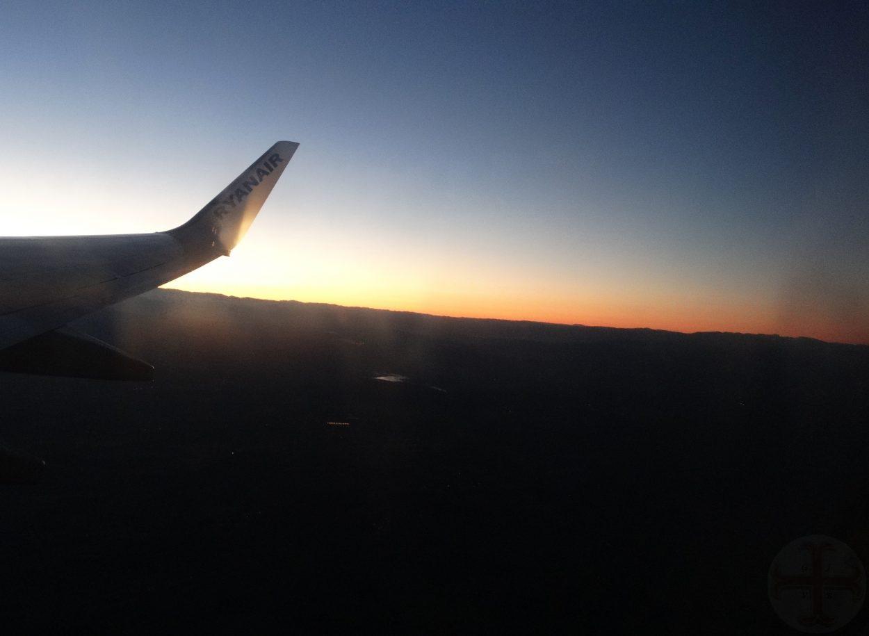 """Afbeelding bij """"Jezelf beter waarnemen"""": je ziet nog net een stuk van de staart van een vliegtuig en een kleurrijke zonsopgang"""