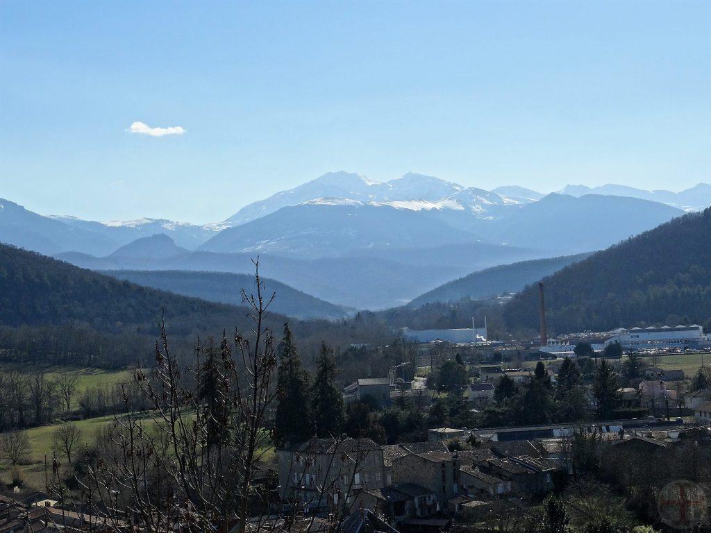 """Afbeelding bij """"Verlies, het leven gaat zijn gang"""": een berglandschap met helderblauwe lucht, dorpje in een dal (Ariège, Frankrijk)"""