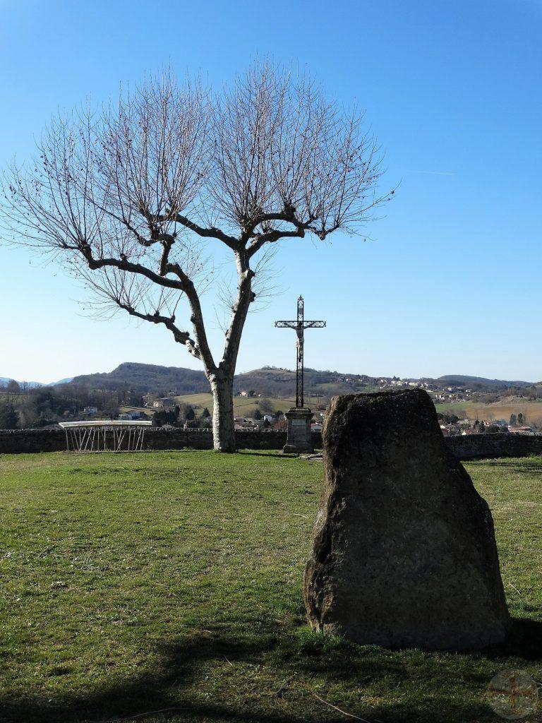 """Afbeelding bij """"Verlies, het leven gaat zijn gang"""": een kruis en een boom met bergen op de achtergrond en een steen op de voorgrond"""