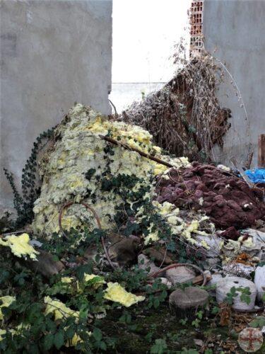 Foto van afval dat is overwoekerd door onkruid: jaloezie overwoekert: jaloezie woekert als onkruid en ondermijnt je zelfvertrouwen